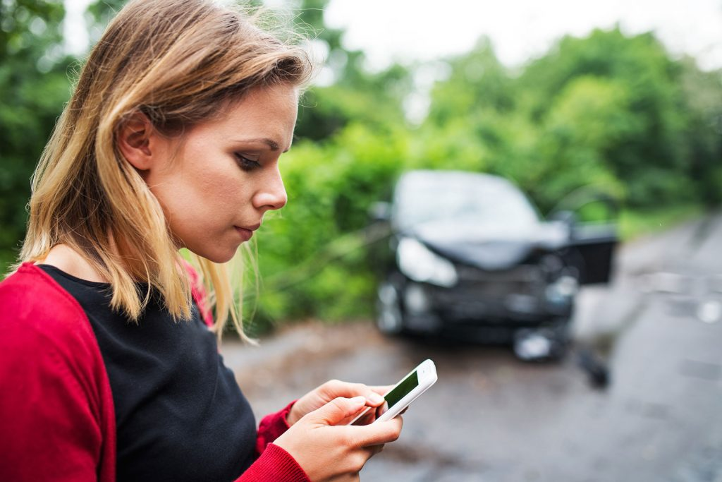 woman-looking-down-at-gapwallet-app-on-phone-in-front-of-wrecked-car